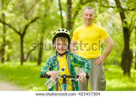 Young boy with a bottle of water is learning to ride a bike with his grandfather - stock photo