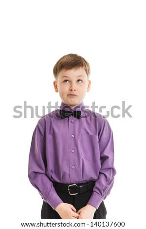 Young boy with a bow-tie looking up thoughtfully - stock photo