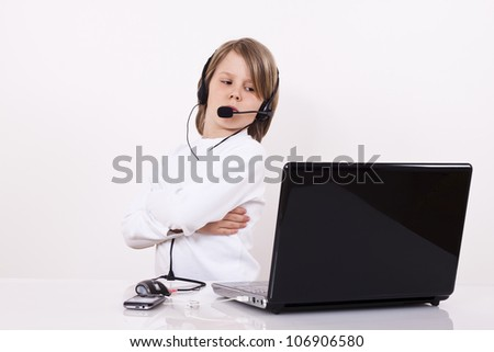 Young boy with a headset looks something on the Internet. - stock photo