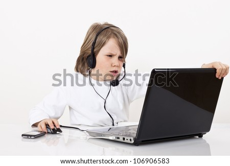 Young boy with a headset looks something on the Internet.