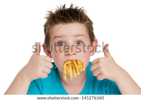 Young boy with a mouth full of chips fries. Isolated on white background.