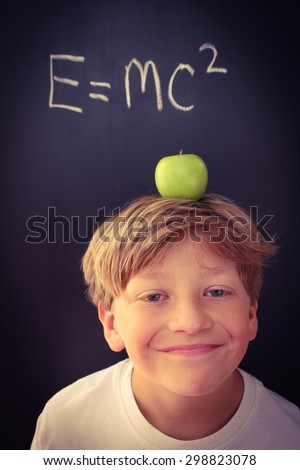 Young boy with a smug look on his face, balancing an apple on his head in front of a mathematical formula - stock photo
