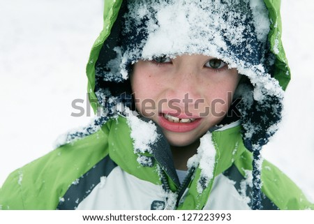 Young Boy with an Unhappy Expression from Falling in Snow