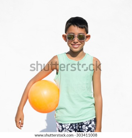 young boy with beach volley ball and sunglasses on white background - stock photo