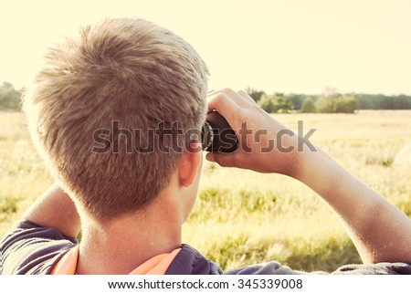 Young boy with binoculars in field looking into the distance. concept for future, discovery, exploring and education - stock photo