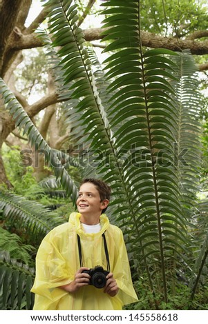 Young boy with camera standing by large fern in forest during field trip - stock photo