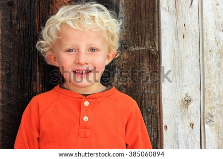 Young boy with curly hair and a rustic wood background. - stock photo