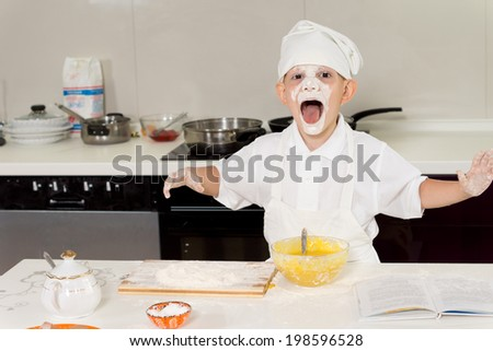 Young boy with flour all over his face and mouth wide open having fun in the kitchen - stock photo