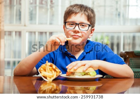 Young boy with glasses eating french fries and a burger at home - stock photo