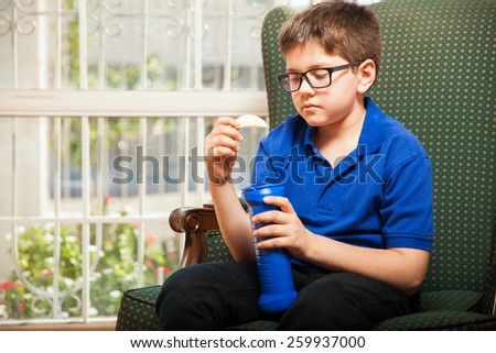 Young boy with glasses eating some chips while relaxing at home - stock photo