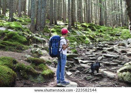 Young boy with her dog in the middle of woods - stock photo