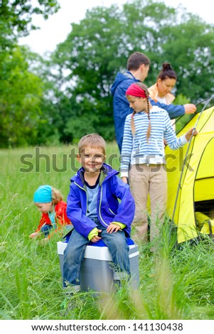 Young boy with his family near tent in camping on the nature