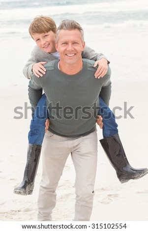 Young boy with his father at the beach - stock photo