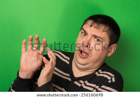 young boy with his mouth and eyes wide and covering her mouth with her hands, expression of surprise, yawning,  - stock photo