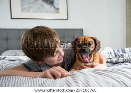 Young Boy with His Sleepy Puggle Dog - stock photo