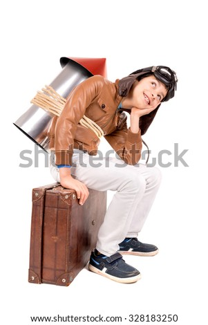 Young boy with home made rocket and suitcase ready for adventure