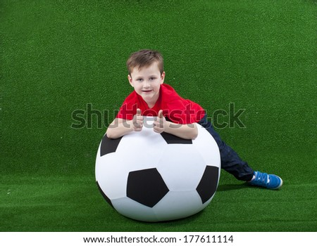 Young boy with huge soccer ball on green background