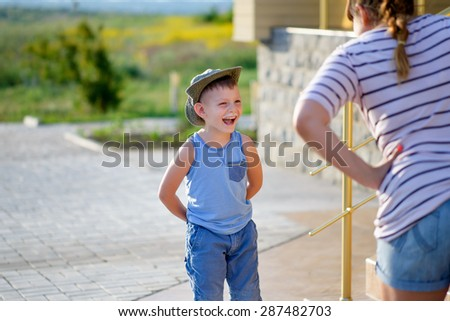 Young Boy with Ice Cream Moustache Standing with Hands Behind Back and Laughing in front of Angry Mother Standing with Hands on Hips Outdoors
