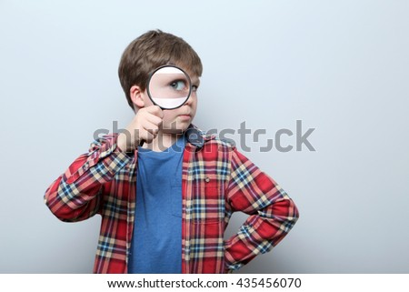 Young boy with magnifying glass on a grey background