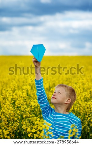 Young Boy with paper Plane against blue sky and Yellow Field Flowers - stock photo