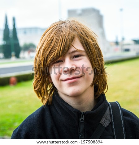 young boy with red hair is smiling and looking happy - stock photo