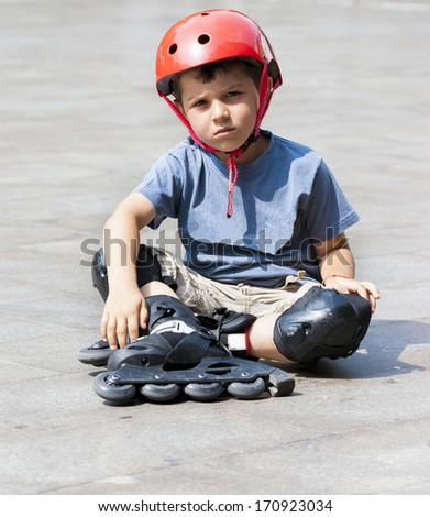 Young boy with rollerblades stopping to tighten up - stock photo