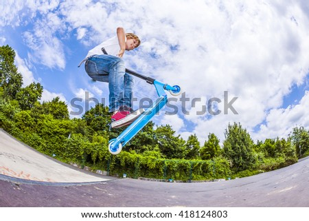 young boy with scooter is going airborne