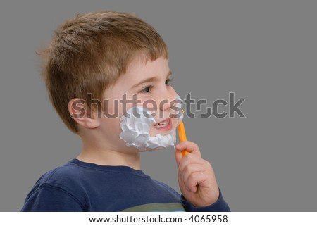 Young boy,with shaving cream on face, removing it with razor, isolated
