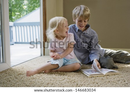 Young boy with sister sitting on carpet with book laughing - stock photo