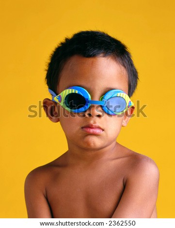 Young boy with swim goggles against yellow background