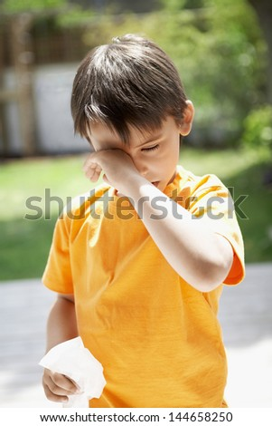 Young boy with tissue paper rubbing eye in backyard - stock photo