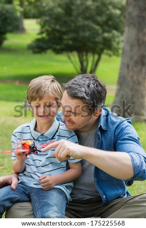 Young boy with toy aeroplane sitting on father's lap at the park - stock photo