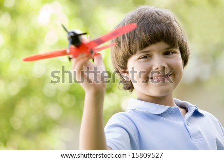 Young boy with toy airplane outdoors smiling - stock photo