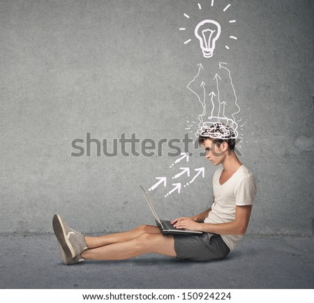 young boy working at the computer sitting on the floor - stock photo