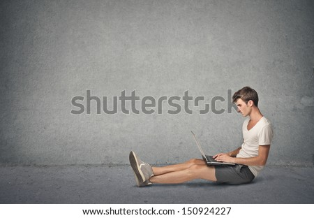 young boy working at the computer sitting on the floor