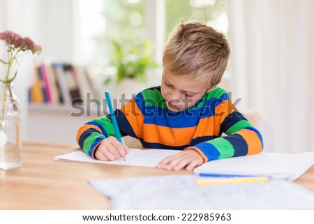 Young boy working on his class homework sitting at a table in front of a window writing in a notebook