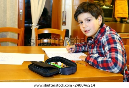 young boy writes on his notebook at home 5