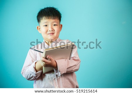 Young boy writing a book