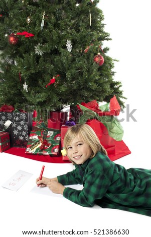 Young boy writing a christmas list by the tree isolated on white background