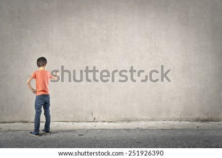 Young boy writing on a blank wall  - stock photo