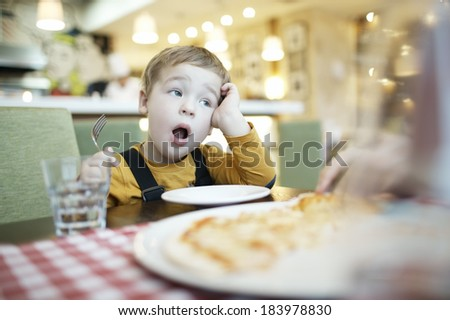 Young boy yawning as he waits to be fed sitting at the dining table with an empty plate in front of him - stock photo