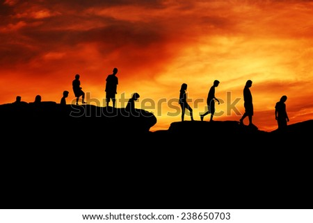Young boys and girls silhouette walking on hill over red sunset for concept background