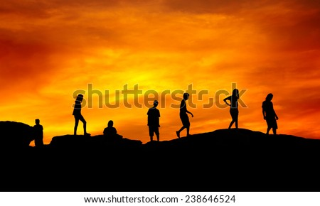 Young boys and girls silhouette walking on hill over sunset
