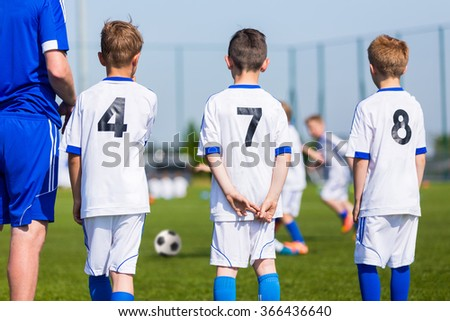 Young boys and soccer coach watching football match. Youth reserve players ready to play football tournament. Football soccer match for children. Boys and coach waiting on a bench. - stock photo