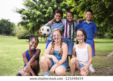 Young boys and sport, portrait of three young children with football looking at camera. Summer camp fun - stock photo