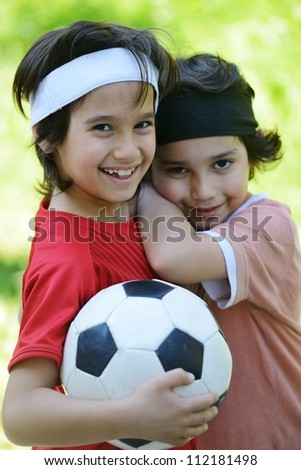 Young boys holding football outside - stock photo