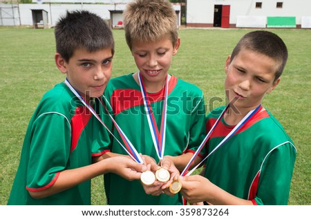 young boys holding  gold medals