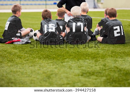 Young Boys In Soccer Football Team With Coach. Motivation Talk Before Soccer Match. Little League Soccer Boys Team. - stock photo