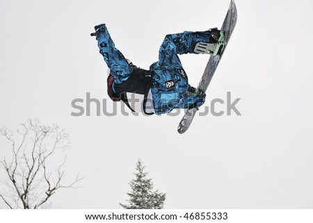 young boys jumping in air ind showing trick with snowboard at winter season