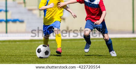Young boys kicking soccer football on the sports field. Youth teams tournament competition - stock photo